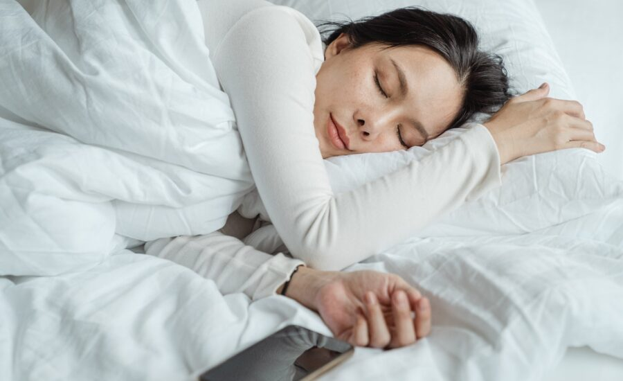 Dame sover i hvid seng