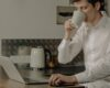 Mand drikker kaffe og kigger på sin pc