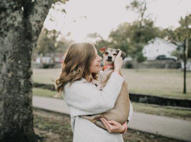 Kvinde står og kæler sin hund